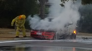 Firefighters extinguish the burning car.