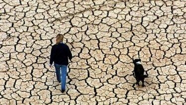 A resident walks along a drought-stricken Lake Eildon in 1998.