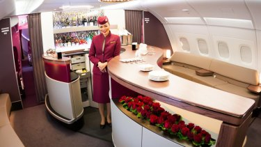 A Qatar Airways cabin crew member at the Airbus A380 First Class bar and  lounge.