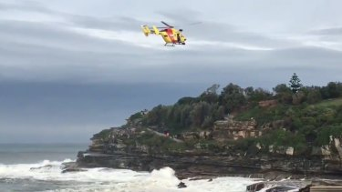 The Westpac Rescue Helicopter searches for a person missing in heavy surf south of Bondi Icebergs.