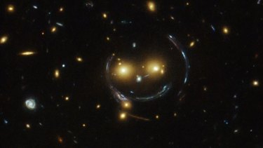 In the center of this image, taken with the Hubble Space Telescope, is the galaxy cluster SDSS J1038+4849 — and it seems to be smiling.