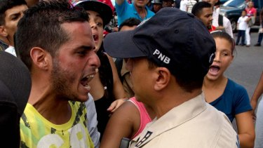 A man who was waiting in line at a grocery store argues with a police officer  in Caracas.
