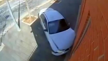 About 2.05pm this afternoon, the driver of a white Holden Commodore was attempting to turn the corner of Anthony Rolfe Avenue onto Gozzard Street in Gungahlin, when he accelerated rapidly in an attempt to complete a burnout and lost control of his car and crashed into Gungahlin police station. Screen grab from ACT Policing Facebook page