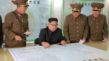 Kim Jong-un consults maps of proposed missile launches to Guam, in this image published by North Korean state media on Tuesday.