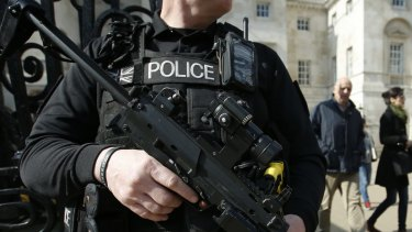 An armed British policeman stands on duty in central London.