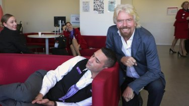 Power nap: Richard Branson and the exhausted Virgin Australia staffer.