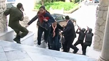 A still image taken from video shows tourists running for cover as armed men stand guard at Tunisia's national museum.
