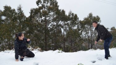 Sally Vo and Eric Huynh, both of Melbourne, enjoy a snow fight on a snowy summer day.