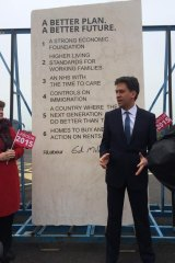 Be careful what you pose for: Ed Miliband with the 'tombstone' of pledges.