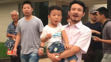 Chinese labour activists Li Zhao and Hua Haifeng (with his son) leave a police station after being released in Ganzhou following their arrest in relation to their investigations into factories used by Ivanka Trump's brand.