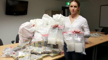A police officer with the cash and drug haul linked to the money laundering syndicate
