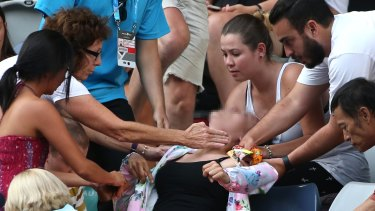 A tennis fan was helped by fellow spectators after she collapsed during Bernard Tomic's match with Denis Istomin.