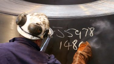 An employee marks a roll of coiled steel inside