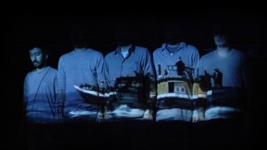 A scene from <i>Manus</i> with a projection of an asylum seeker boat