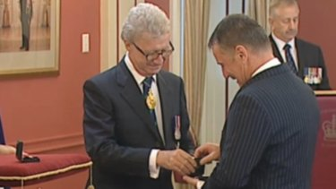 Queensland Governor Paul de Jersey presents a bravery award to John Tyson, who received it on behalf of his late son Jordan Rice. Jordan died a hero in the 2011 floods when he insisted his younger brother, then aged 10, be rescued first.