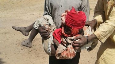 A man carries an injured child following a military air strike at a camp for displaced people in Rann, Nigeria.