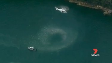 A helicopter hovers over the water near where the seaplane is believed to have gone down.