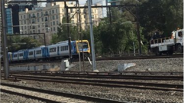 A train comes dangerously close to a maintenance vehicle between Flinders and Richmond stations on Saturday.