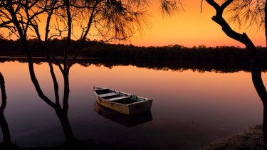 A boat on the Noosa River during sunset; Mt Coonowrin.