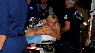 Paramedics treat Brett Connellan at Bombo Beach after the attack.