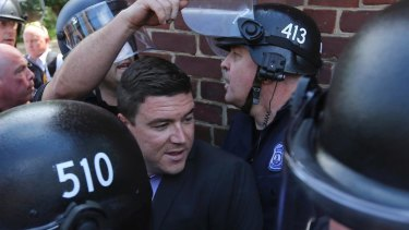 Unite the Right rally organiser Jason Kessler is escorted by police after his press conference was disrupted by protesters in August.
