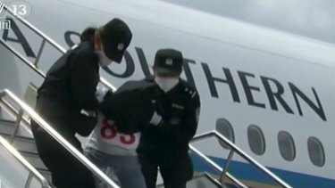 One of the Uighurs is taken off a plane in China.