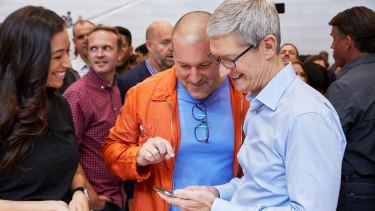 Apple's Tim Cook and Jony Ive look at the new iPhone X in the hands on area.