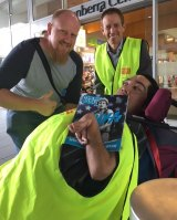 Greens MLA Shane Rattenbury sells The Big Issue with vendor Tau (right) while getting the thumbs up from a prospective customer.