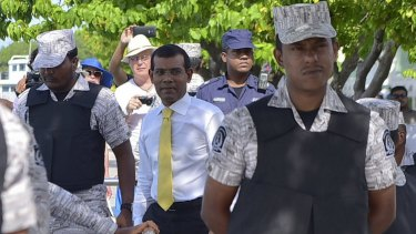 Facing 13 years in prison ... Former  Maldives president Mohamed Nasheed, centre,  after appearing at the High Court in Male, Maldives on September 9.