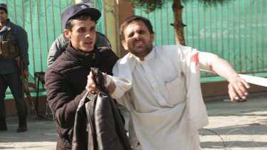 A wounded man is assisted after the attack in Kabul on Saturday.