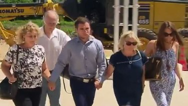 Thomas Keating (centre) arriving at Phuket police station with members of his family, and the family of his late girlfriend Emily Collie.