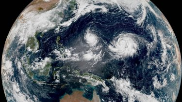 Twin typhoons spin in the western Pacific, far to Australia's north.