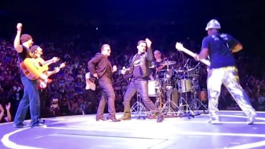 Bono with U2 tribute band 'Acrobat' on stage in Toronto. The cover band was invited on stage to play 'Desire' during an official U2 gig.