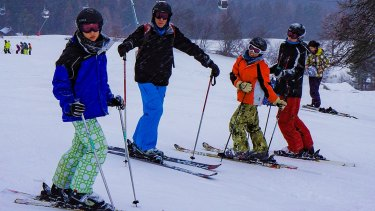 Robert Lake and his sons skiing in Austria in 2012. He always gets travel insurance for foreign ski trips but wouldn't consider it in Australia.