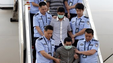 Six fugitives accused of economic crimes are taken back to China under escort from Indonesia in June 2015 as part of Operations Fox Hunt and Skynet.