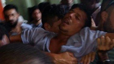 An asylum seeker collapsing after police enter the Manus Island detention centre on Manus Island on Thursday.