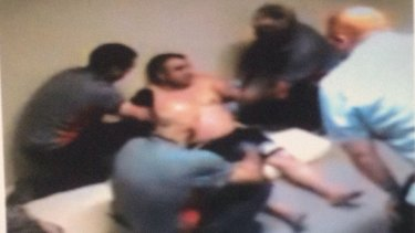 CCTV shows security guards restraining a detainee at Maribyrnong Immigration Detention Centre.