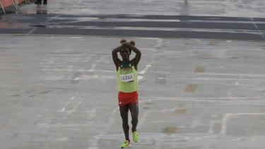 Moment of protest: Ethiopia's Feyisa Lilesa crosses his arms as he crosses the finish line.