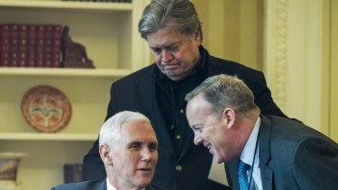 Steve Bannon, chief strategist for US President Donald Trump, stands behind Vice-President Mike Pence and White House press spokesman Sean Spicer in the Oval Office.