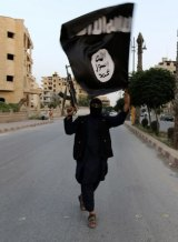 A member of the Islamic State in Iraq and the Levant - the forerunner to the Islamic State - waves an ISIL flag.