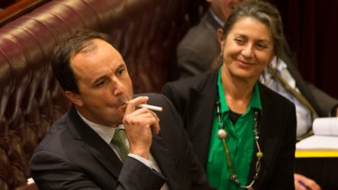 Greens MP Jeremy Buckingham lights an e-cigarette in the NSW Upper House to show how lax the laws are that govern the devices.