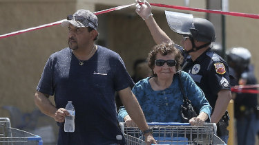 Walmart customers are escorted from the store after a gunman opened fire on shoppers.
