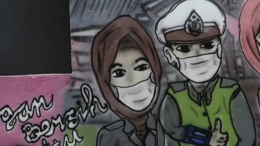 A man walks past a coronavirus awareness mural at Rawa Pasung village in Bekasi on the outskirts of Jakarta.
