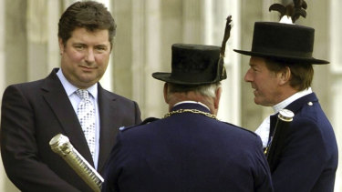 A 2004 file photo shows Michael Fawcett, left. the former close aide to Britain's Prince Charles stepped down temporarily from his role as chief executive of a royal charity amid reports that he helped secure an honour for a Saudi donor.