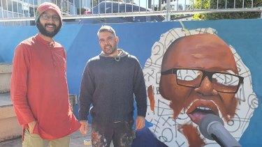 Gabba councillor Jonathan Sri (left) and artistWarraba Weatherall in front of an art mural dedicated to the late Brisbane Aboriginal activist Sam Watson.