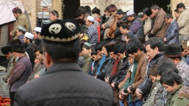 Uighur Muslims attend Friday prayers at the central mosque in Hotan, Xinjiang, where they are under constant state surveillance.