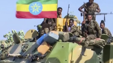 Ethiopian military sitting on an armored personnel carrier next to a national flag, on a road in an area near the border of the Tigray and Amhara regions of Ethiopia.