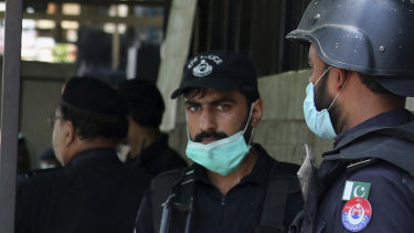 Police officers gather at an entry gate of a district court following the killing of Tahir Ahmed Naseem who was accused of insulting Islam, in Peshawar, Pakistan.