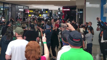 Several dozen anti-lockdown protesters sing John Farnham's 'You're The Voice' as part of their protest at Chadstone shopping centre.