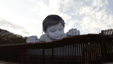 French artist JR, aiming to prompt discussions about immigration, erected a giant cut-out photo of a Mexican boy peering over a wall into the US from Tecate, California.